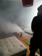 A pest control technician fogging a bedroom