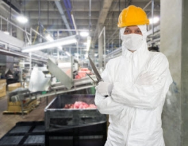 A worker in protective clothing in a food processing plant.
